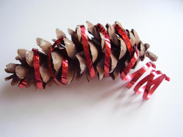 Kids Christmas craft with pine cone and ribbon