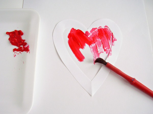 Place the stencil on white paper to make a heart painting