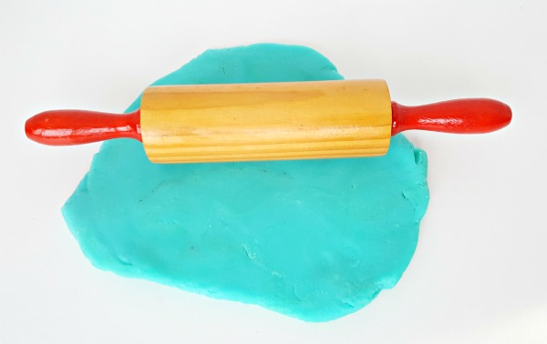 Roll play dough with a rolling pin in a kids sensory activity