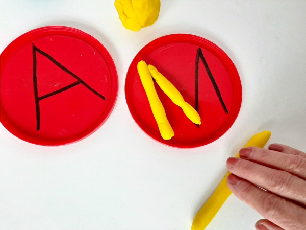 Roll play dough in strips to make letters