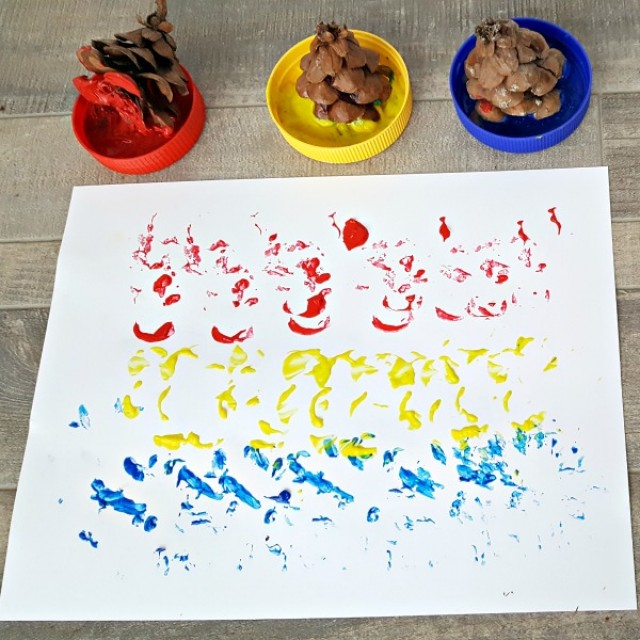 Kids process art painting activity with pine cone tops
