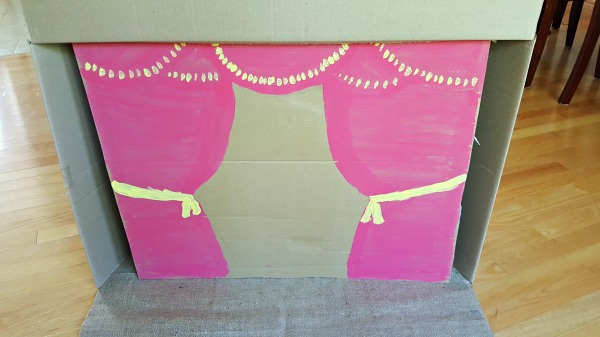Paint a curtain design on cardboard for the diy marionette theater