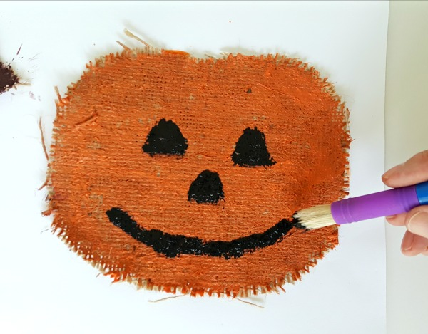 Paint eyes nose and mouth on the burlap pumpkin