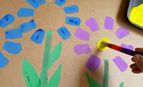 Paint flowers on a cardboard backdrop for a homemade marionette theater.