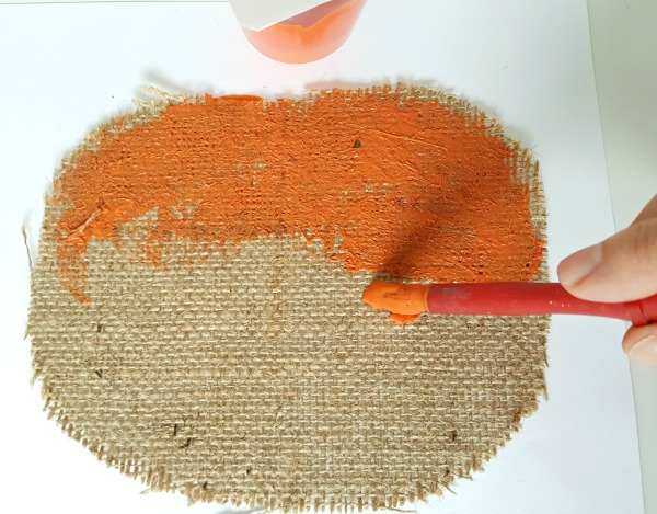Paint the pumpkin shape cut from the burlap with orange craft paint