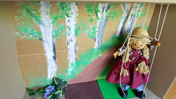 Puppet show with marionette in a cardboard box theater you can easily make.