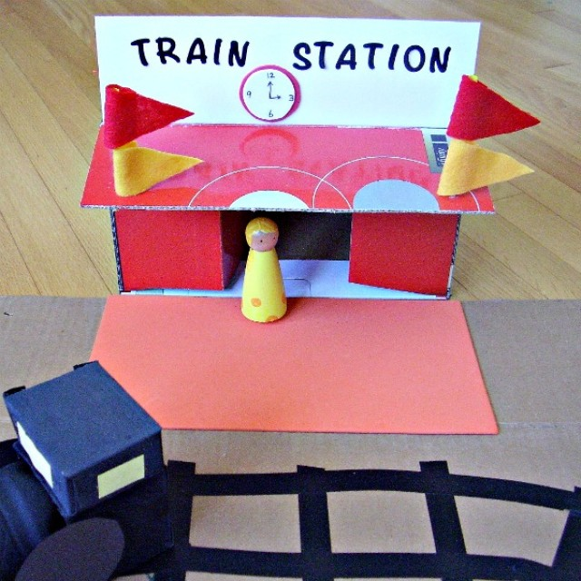 Small world play with a homemade cardboard box train station