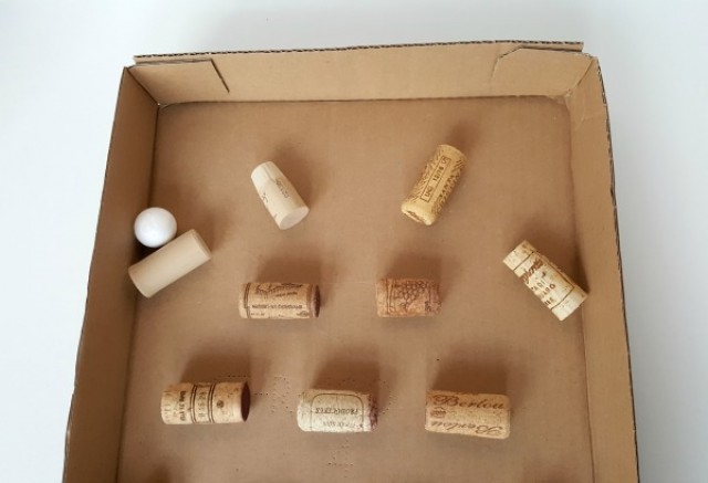 Make a marble maze with corks and a cardboard box for a fun activity for kids
